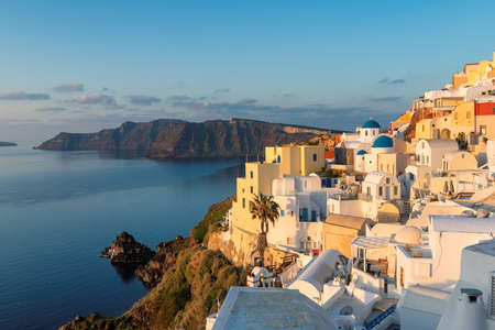 Sunrise at blue and white domed churches on Santorini Greek Island, Oia town, Santorini, Greece.