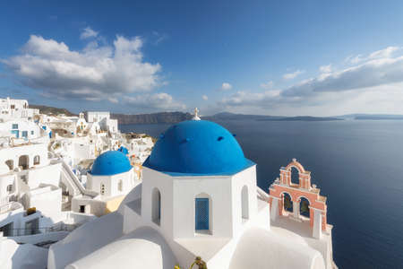 Beautiful Romantic view of Greek orthodox church with blue domes and sea in Santorini island, Greece.
