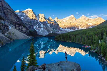 Beautiful sunrise under turquoise waters of the Moraine lake with snow-covered peaks in Banff National Park, Canada