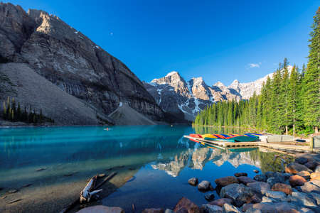 Beautiful sunrise under turquoise waters of the Moraine lake in Canadian Rockies, Banff National Park, Canada