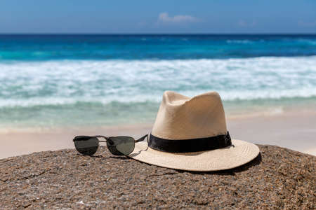 Beach accessories, straw hat and sunglasses on tropical beach 免版税图像