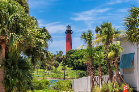 Jupiter lighthouse at sunny summer day and palm trees around, West Palm Beach, Florida 免版税图像
