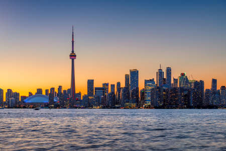 Skyline of Toronto at sunset with CN Tower over Ontario Lake