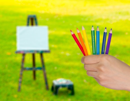 Many colored pencils in hand at park photo