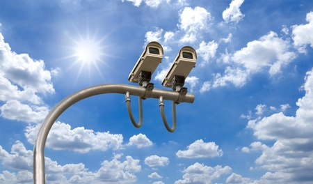 Outdoor Security cctv cameras under Sun shine and White cloud in blue sky Stock Photo - 10455692