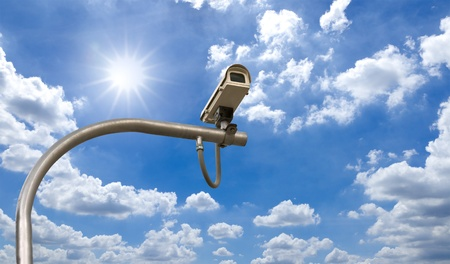 Outdoor Security cctv cameras under Sun shine and White cloud in blue sky photo