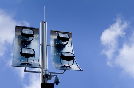 Outdoor security cameras and spotlight against beautiful blue sky photo