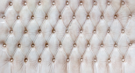 Closeup texture of vintage cream leather sofa for background photo