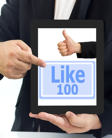 Businessman show a tablet pc and the like button 100 time photo