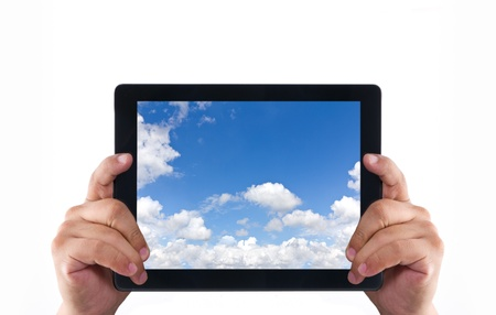 Hands holding a tablet pc and beautiful blue sky and clouds Stock Photo