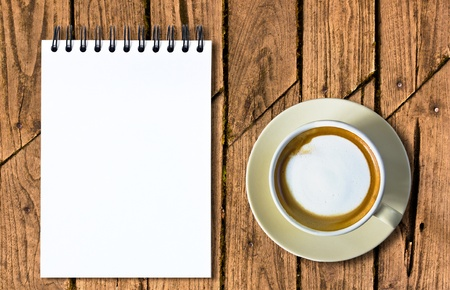 Coffee and white sketch book on old wood table