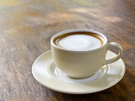 Coffee cappuccino cup on wood table in morning photo