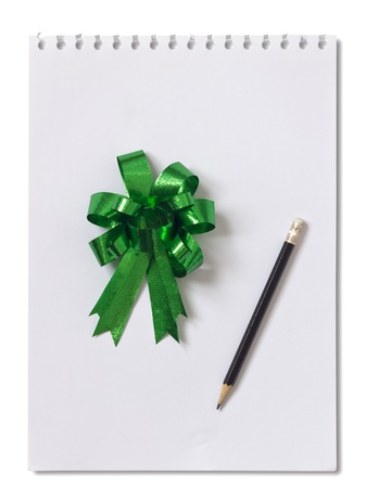 Green bow on  paper and pencil isolated on the white background photo
