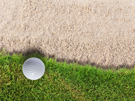 Golf ball on green grass near sand bunker