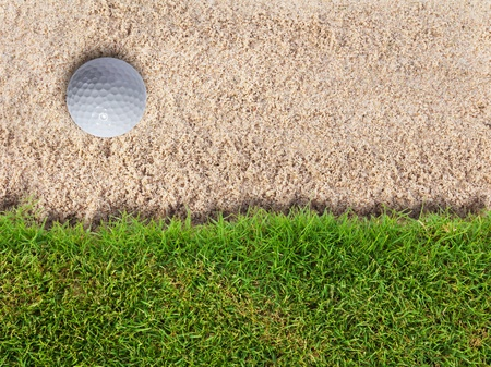 Golf ball in sand bunker near fresh green grass