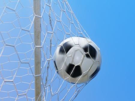 Football spinning in goal against blue sky