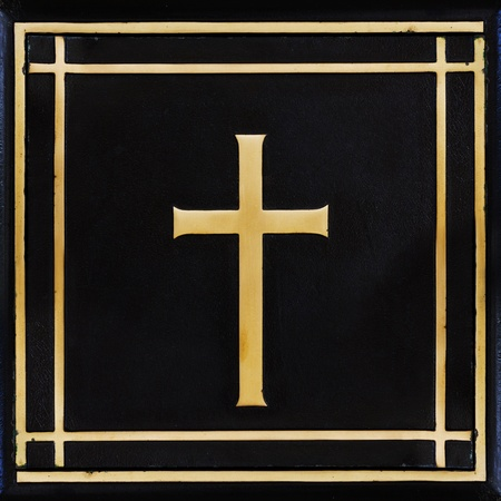 Golden cross, symbol of the Christian faith on the black background photo