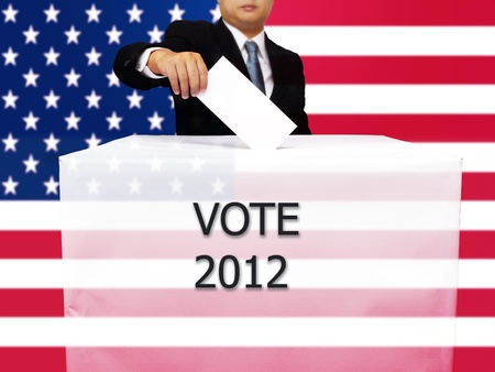 Gentleman hand putting a voting ballot in slot of white paper box and flag of USA photo