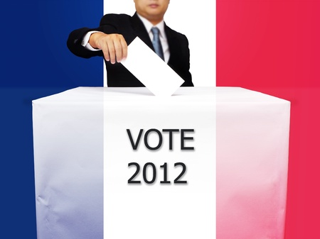Gentleman hand putting a voting ballot in slot of white paper box and flag of France Stock Photo - 13920186