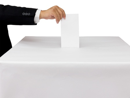 Gentleman hand putting a voting ballot in slot of white box isolated on white photo