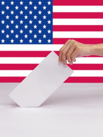Lady hand putting a voting ballot in slot of white box isolate and flag of USA photo