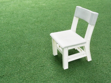 White child chair on green grass Stock Photo - 13920296