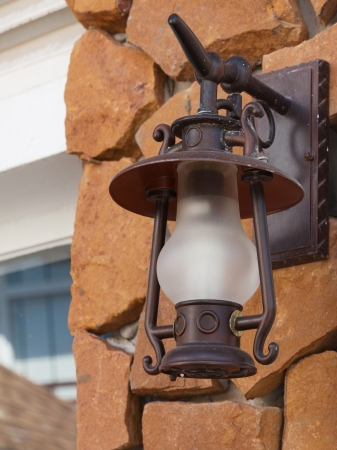 Old-fashion lamp hanging on sand stone wall photo