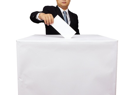 Gentleman hand putting a voting ballot in slot of white box isolated on white Stock Photo