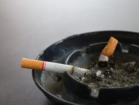 Closeup burning cigarette in ashtray and smoke on the table photo