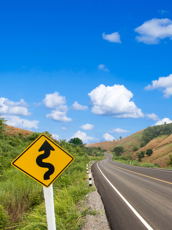 country winding road sign with blue sky Stock Photo