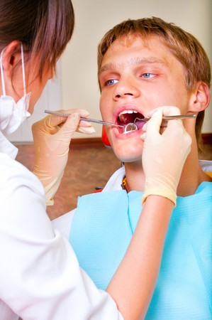 Young dentist giving a treatment to her patient photo