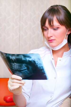 Young dentist looking at x-ray picture photo