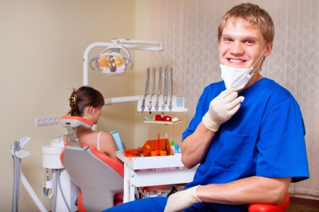Young dentist in his office looking at the viewer photo