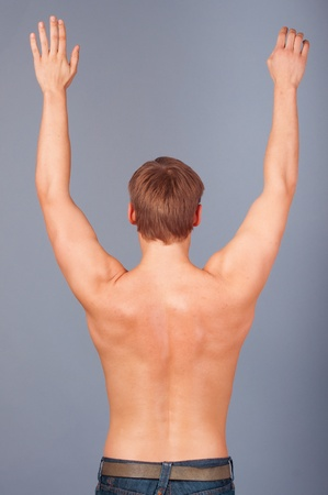 Rear view of a muscular young man with his arms raised