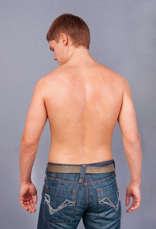 man rear view: Rear view of a muscular young man with his arms raised