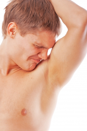 closeup of young man sniffing his armpit isolated on white background photo