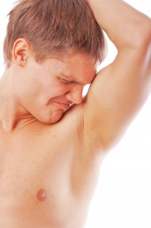 armpit: portarretrato de joven oliendo su axila aislada sobre fondo blanco
