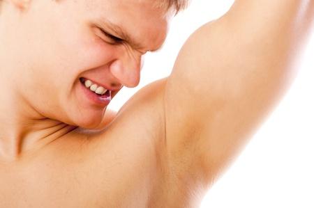 axila: portarretrato de joven oliendo su axila aislada sobre fondo blanco