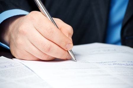 closeup of businessman`s hand signing contract photo
