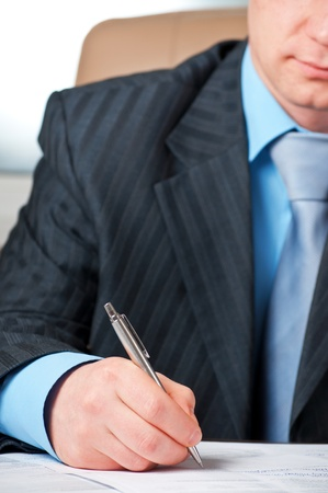 undersign: closeup of businessman`s hand signing contract