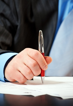 subscribing: businessman with pen signing contract