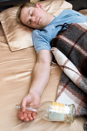 A young man sleeping on the couch with a bottle of wiskey photo