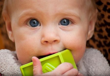 facing the camera: baby holding a green block facing camera Stock Photo
