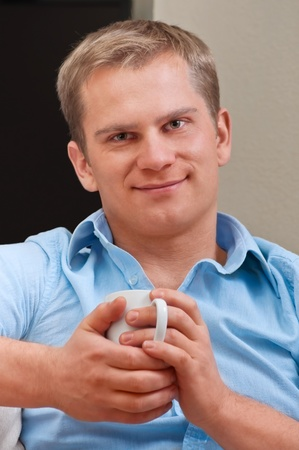 Portrait of a happy young man with cup of coffee - Indoor Stock Photo - 9000039