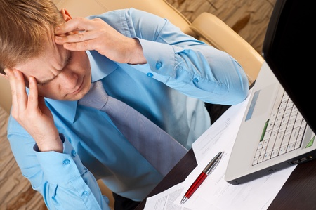 Portrait of a young businessman with headache Stock Photo