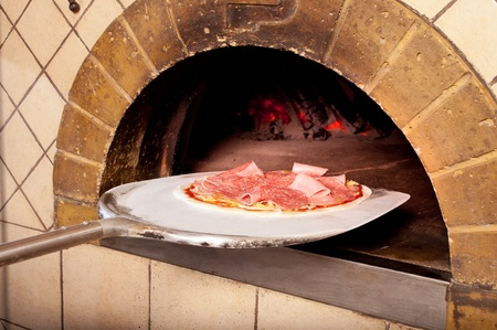 Baked pizza by the fire in traditional oven Stock Photo
