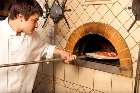 pizza oven: A process of preparing pizza by a chef