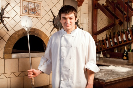 A young chef standing next to oven - indoor Stock Photo - 9583101