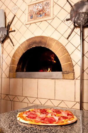 Delicious pizza from wood fired traditional oven in a restaurant Stock Photo