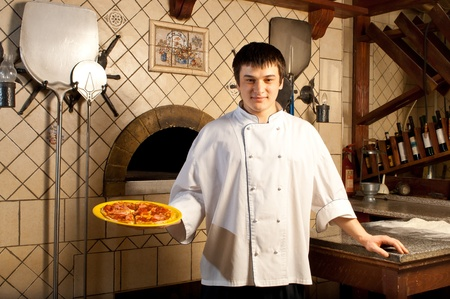pizza base: A young chef standing next to oven - indoor